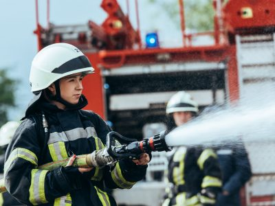 female firefighter with water hose extinguishing fire on street